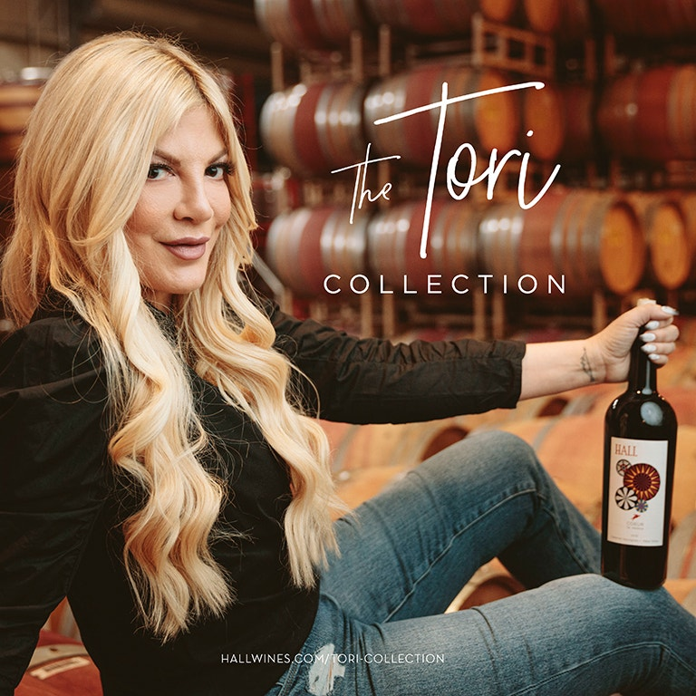 Actress & Author, Tori Spelling photo image holding a bottle of HALL Wines Cabernet